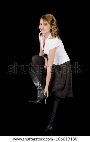 A cute and fresh-face young woman is removin her black patent leather boots. - stock photo