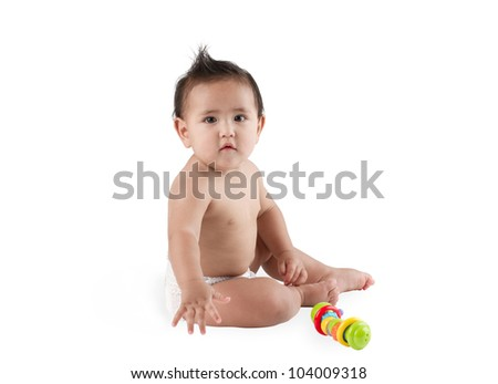 A cute baby boy sitting on the floor with toy - stock photo