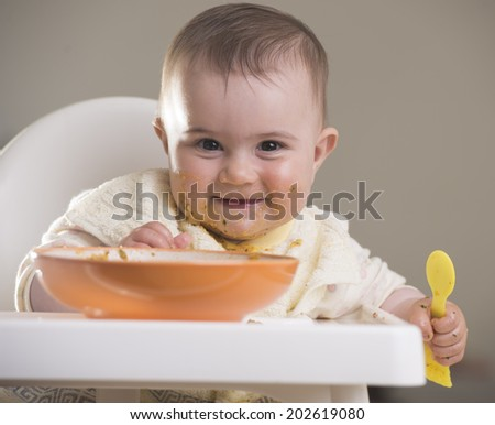 a cute baby girl smiling during meal time - stock photo