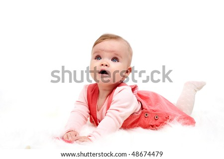 A cute baby smiling on a bed - stock photo