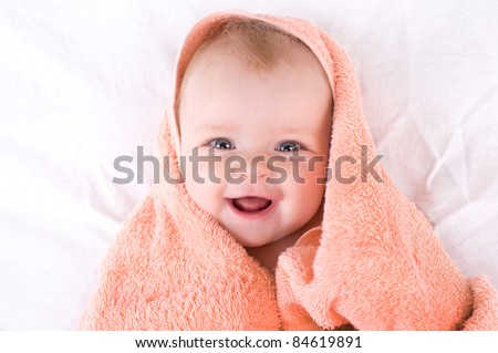 A cute baby wrapped in a towel.