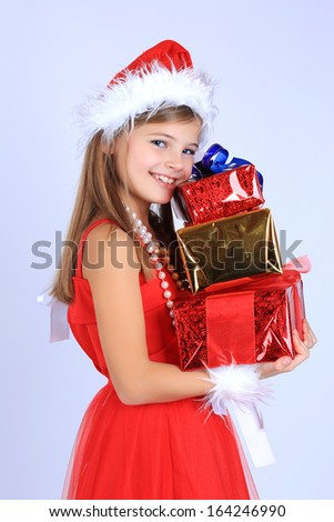 A cute beautiful young girl with long hair in a red dress and santa hat holding christmas presents gift boxes smiling