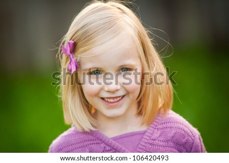 A cute blonde little girl is smiling at the camera.  She is wearing a pink sweater.