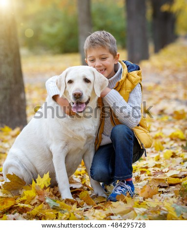 A cute boy and his dog Labrador retriever posing in autumn park. Yellow and orange leaves around.