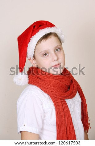 A cute boy in a red christmas hat and scarf