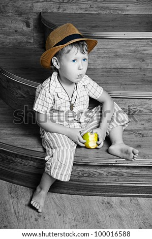 A cute boy with an apple in his hand sitting on the steps. - stock photo
