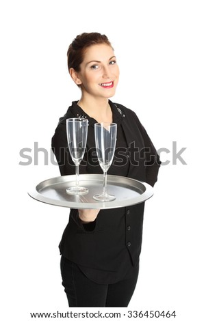 A cute brunette waiter serving two glasses of champagne on a serving tray, wearing a black shirt with a black vest. White background. - stock photo