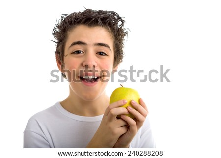 A cute Caucasian child wearing a long sleeved white shirt holds a yellow apple with both hands - stock photo