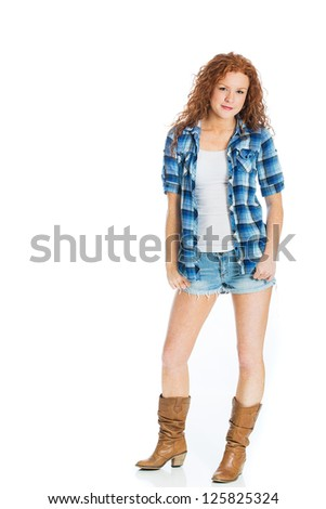 A cute country girl with natural red, curly hair wearing short denim shorts. - stock photo