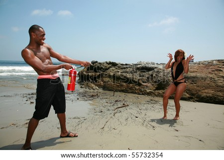 a cute couple play with a fire extinguisher on the beach - stock photo