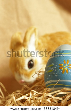 A cute Easter bunny is blurred in the background with the focus on the egg sitting in the paper shred. - stock photo