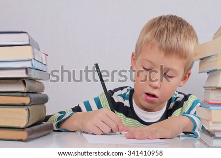 A cute eight years old school boy doing homework surrounded by books at the library