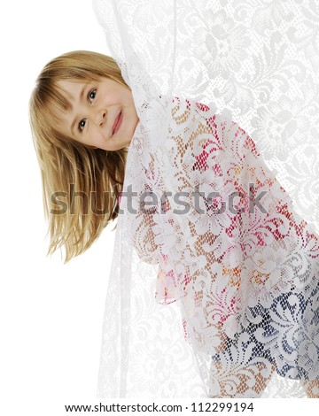 A cute elementary girl peeking her head out from behind a lace curtain.  On a white background.