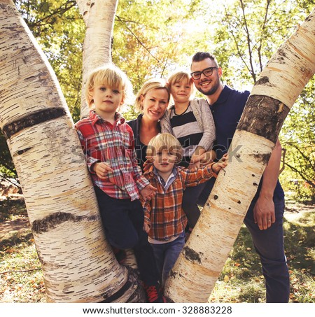 a cute family posing on a tree in a park toned with a retro vintage instagram filter effect app or action - stock photo