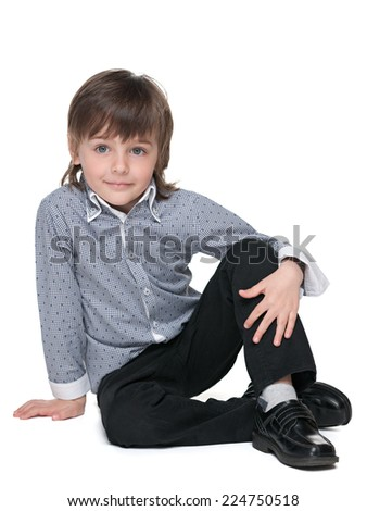 A cute fashion little boy sits on the white background