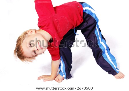 A cute four year old boy wearing red and blue bending over to touch his right toes. - stock photo