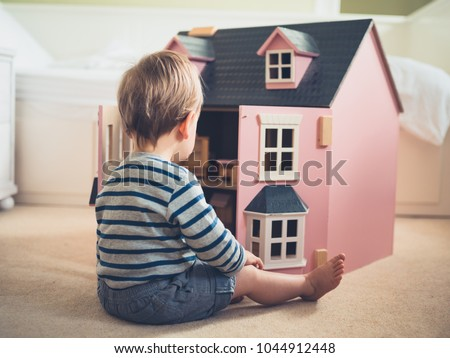 A cute gender confident little boy is busting stereotypes and socially imposed expectations by playing with a big pink doll house and having a great time