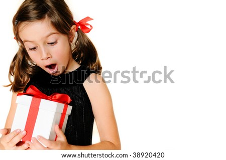 A cute girl excited about a gift, copy space - stock photo