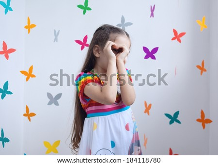 A cute girl holding hands in a shape of heart, playroom, bright background of paper butterflies - stock photo