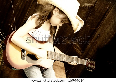 A cute girl playing her guitar, (sepia toned) - stock photo