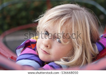 A cute girl resting on a climbing frame in a playground