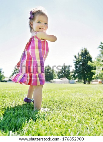 a cute girl running in a local park giggling at the camera - stock photo