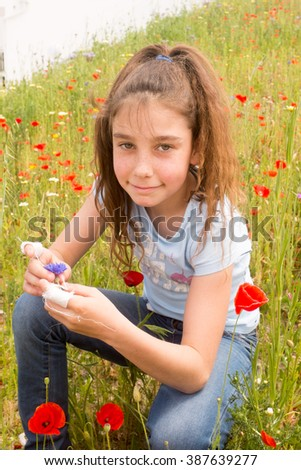 A cute  happy girl holding a flower in the green meadow on a sunny summer day