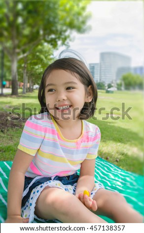 A cute happy little girl sitting smiling and laughing at park, filtered color tone