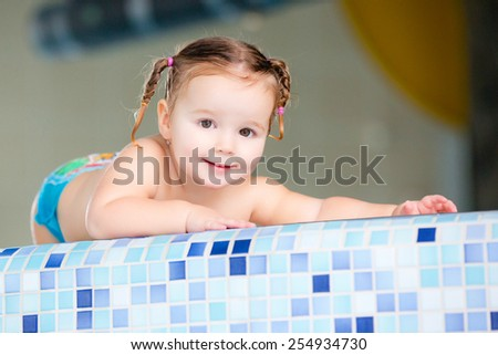A cute happy young female girl child baby relaxing on the side of a swimming pool. - stock photo