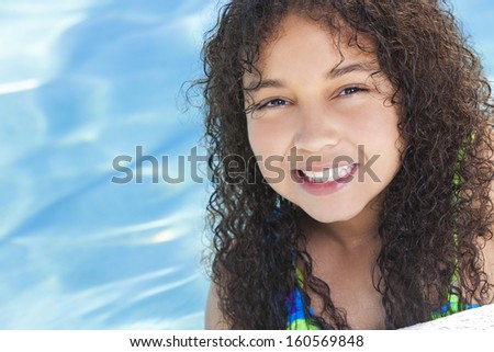 A cute happy young interracial African American girl child relaxing on the side of a swimming pool smiling - stock photo