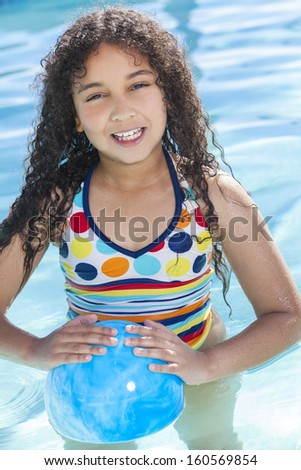 A cute happy young mixed race African American girl child playing in a swimming pool smiling with a blue ball - stock photo