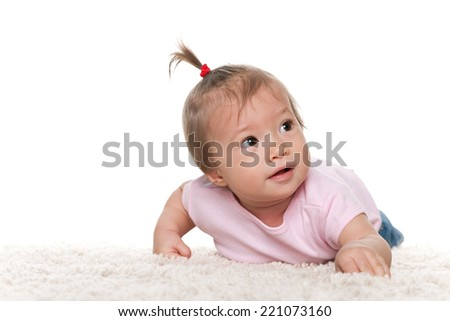 A cute infant girl is lying on the white carpet