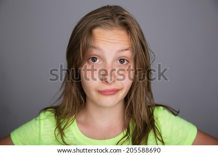 A cute kid with an expression of doubt on her freckled face - stock photo