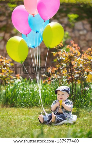 A cute little baby boy sittting in the grass in summertime - stock photo