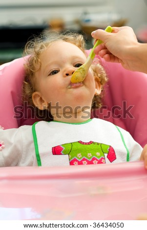 A cute little baby fed by her mother, eating spinach. - stock photo