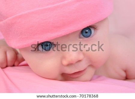 A cute little baby girl is staring up and is on a pink blanket. She is wearing a pink hat and has big blue eyes. Use it for a child, parenting or love concept. - stock photo
