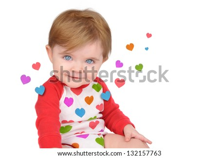 A cute little baby is sitting with hearts from the red clothing floating away on a white isolated background for a love concept.