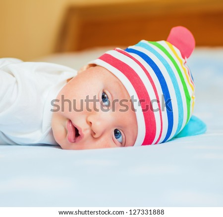 A cute little baby is wearing a white hat. The baby could be a boy or girl and has blue eyes. use it for a parenting or love concept. - stock photo