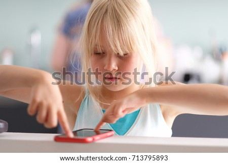 A cute little blond girl playing a game on the phone