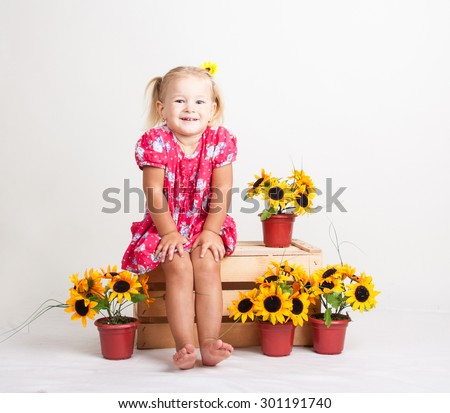 A cute little blond girl sitting barefoot on a wooden box with sunflowers. Children's portrait on a white background - stock photo