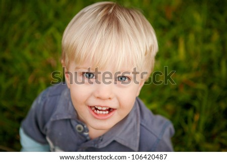 A cute little blonde 1 year old boy outdoors looking up at the camera with a big smile.