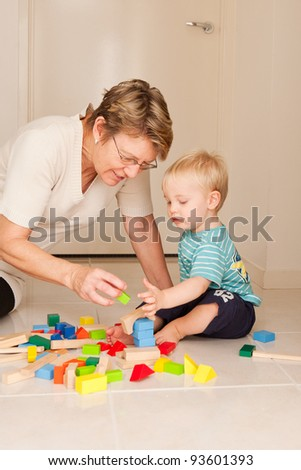 A cute little blong haired blue eyed boy plays with his Nanny, grandmother, au pair. - stock photo