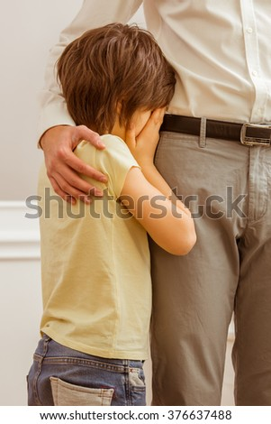 A cute little boy crying while his father hugging him, cropped - stock photo