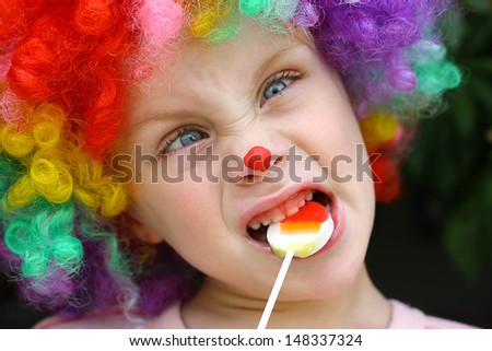 A cute little boy dressed up in a clown costume, making a silly face and eating a lollipop - stock photo