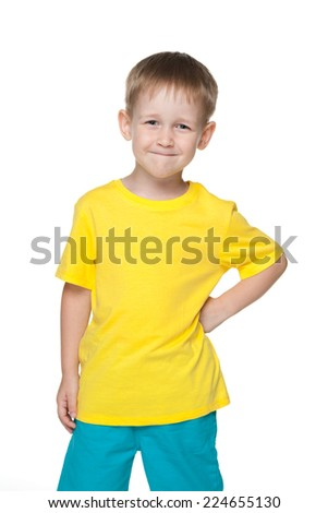 A cute little boy in a yellow shirt stands against the white background