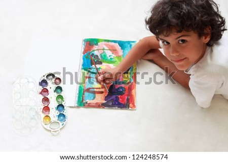 A cute little boy is drawing a picture - stock photo