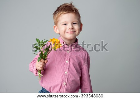 A cute little boy is dressed in a checked pink shirt. A kid with bright blue eyes is holding yellow flower.Studio shot - stock photo