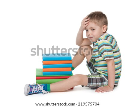A cute little boy is sitting on the floor near the pile of books on the white background