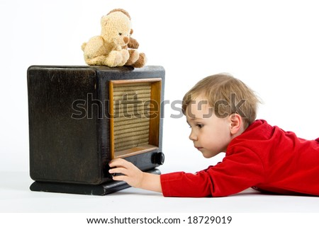 A cute little boy playing with a vintage radio.