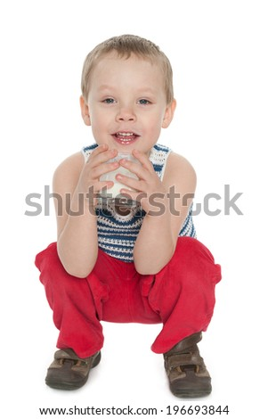 A cute little boy with a glass of milk on the white background - stock photo